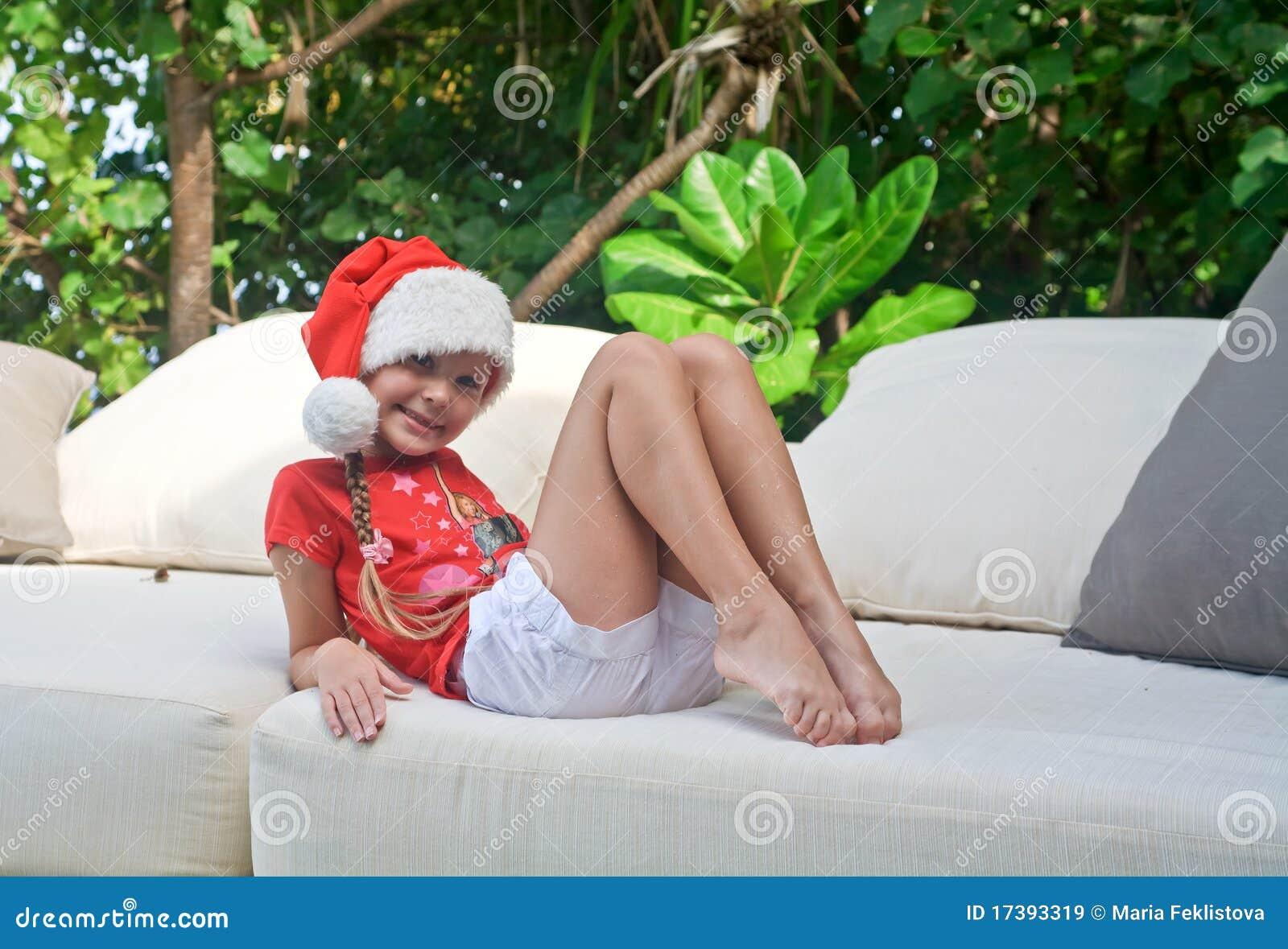 Meisje in de hoed van de Kerstman onder tropische bomen