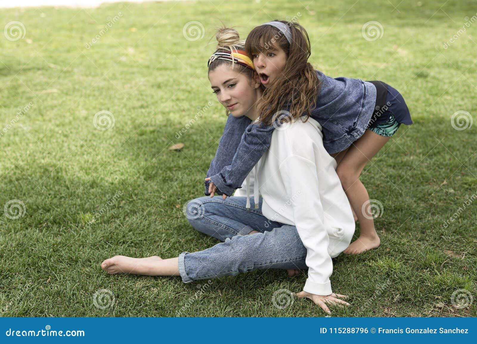 Meisje die achter haar zuster koesteren