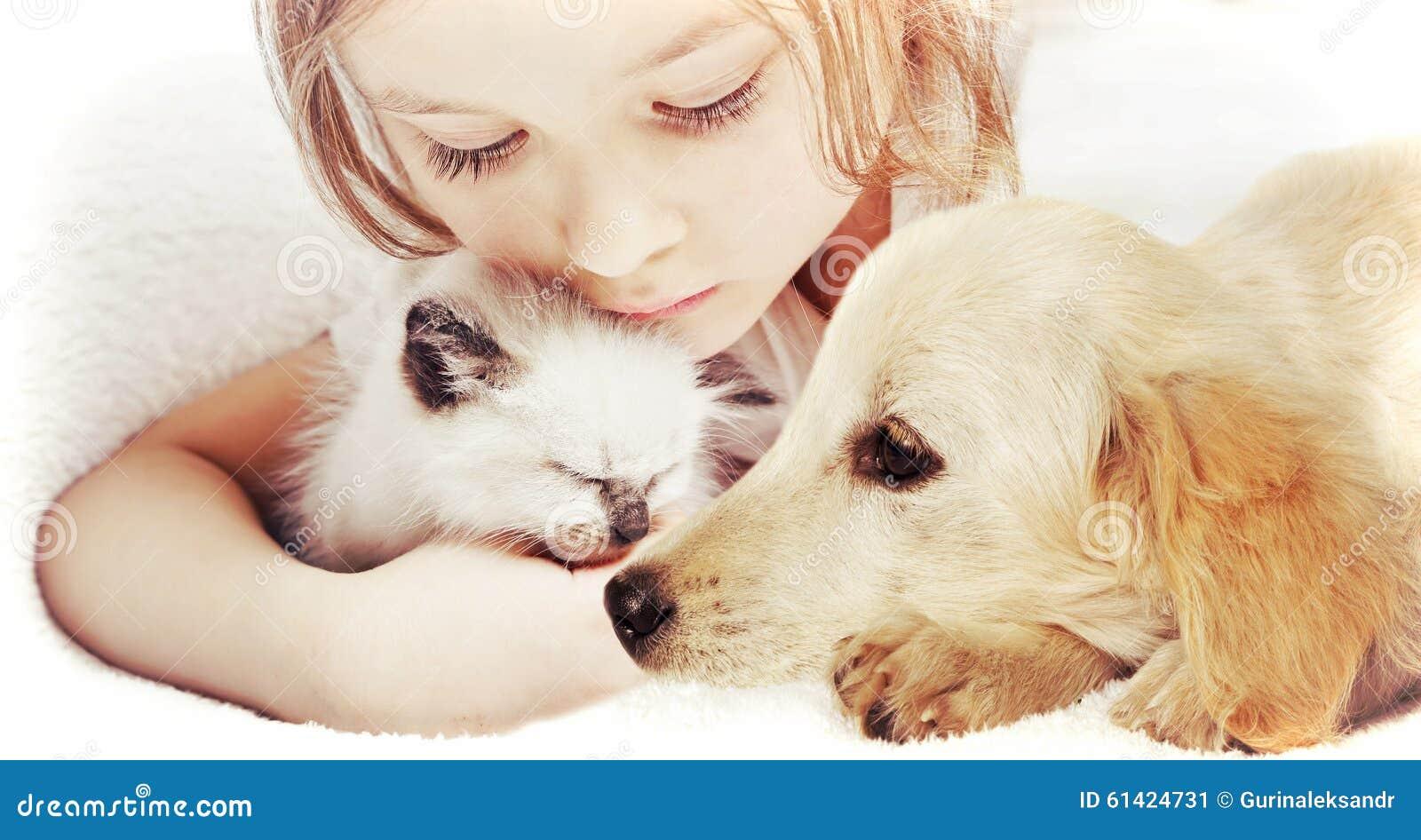 Meisje die affectionately katje en Puppy koesteren