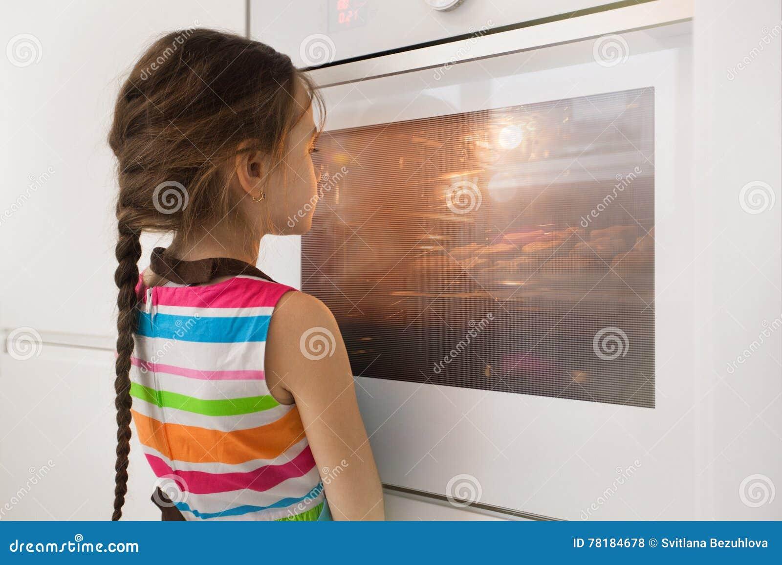 Meisje die dichtbij de keukenoven op eigengemaakte koekjes wachten
