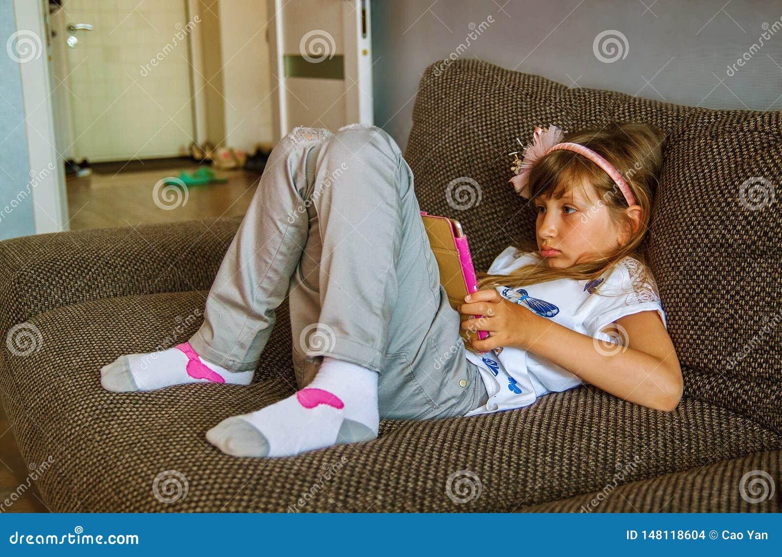 Meisje die digitale tablet op bank thuis gebruiken