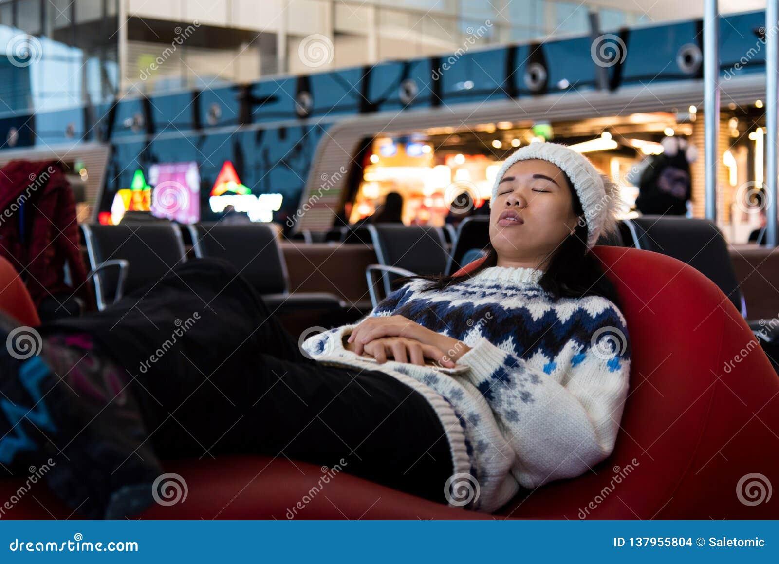 Meisje die een dutje nemen terwijl het wachten bij de luchthaven