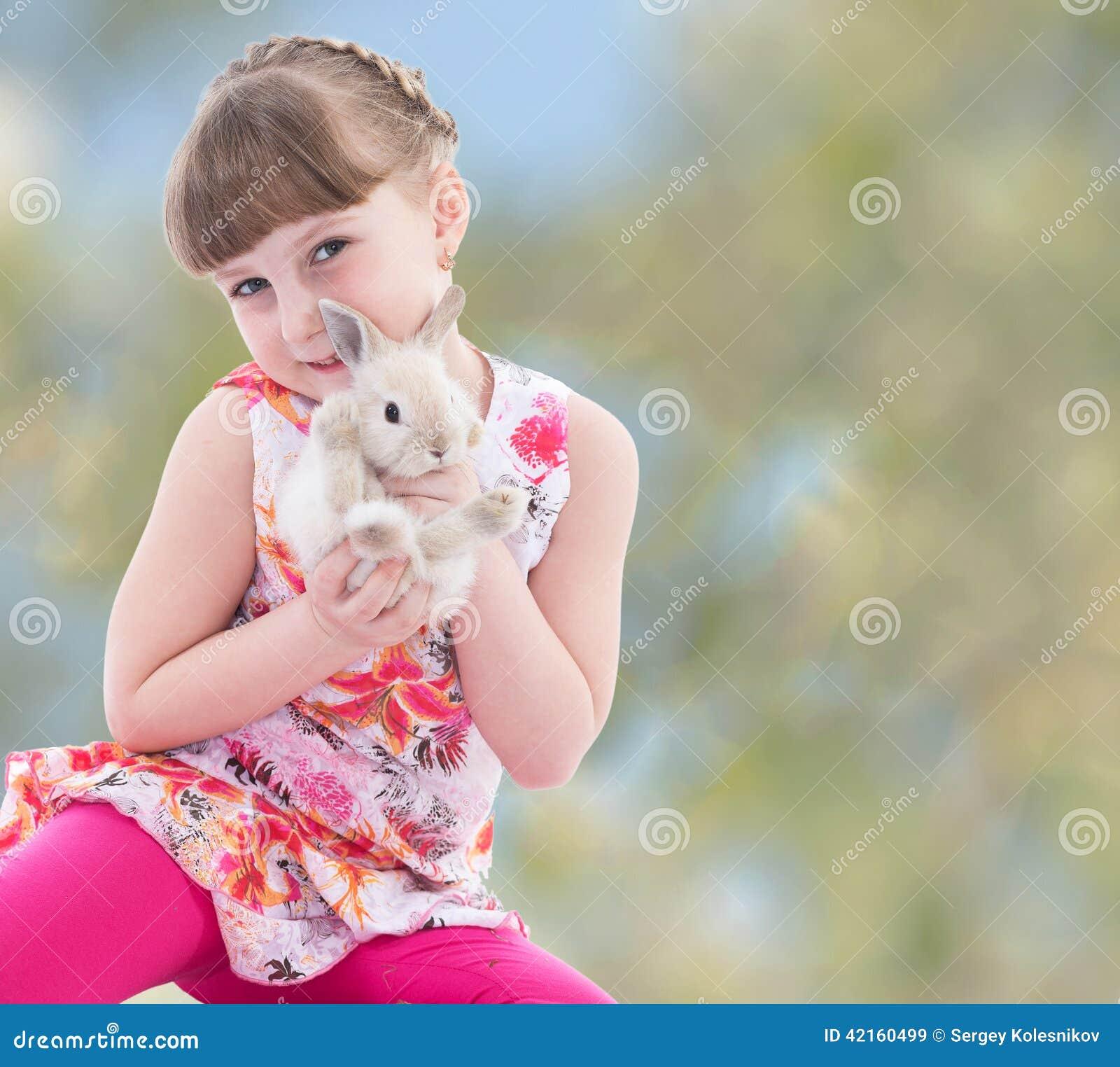 Meisje die een konijn kussen