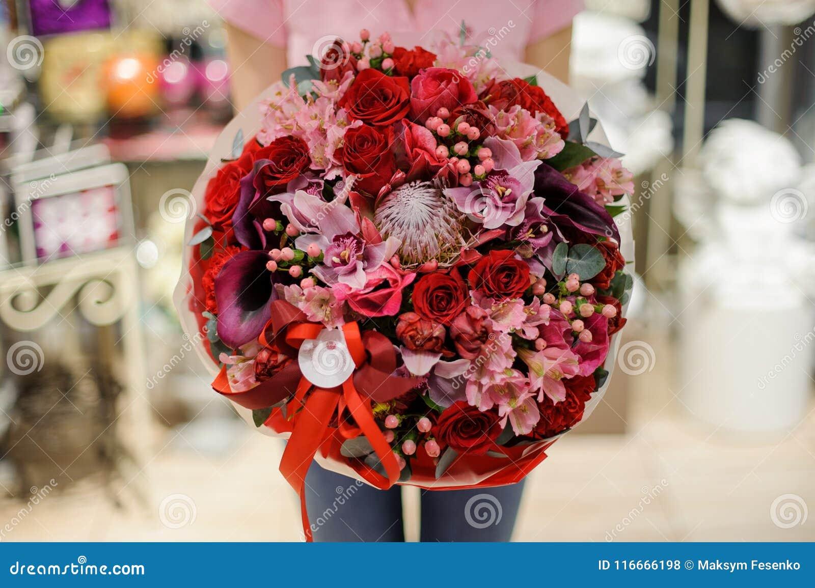 Meisje die een mooi helder boeket van rozen, orchideeën houden en