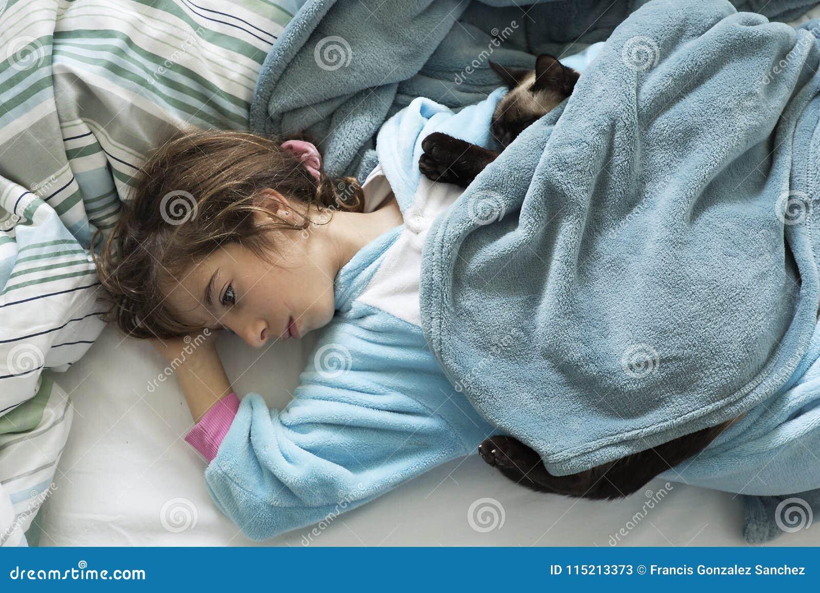 Meisje die en over het bed liggen denken