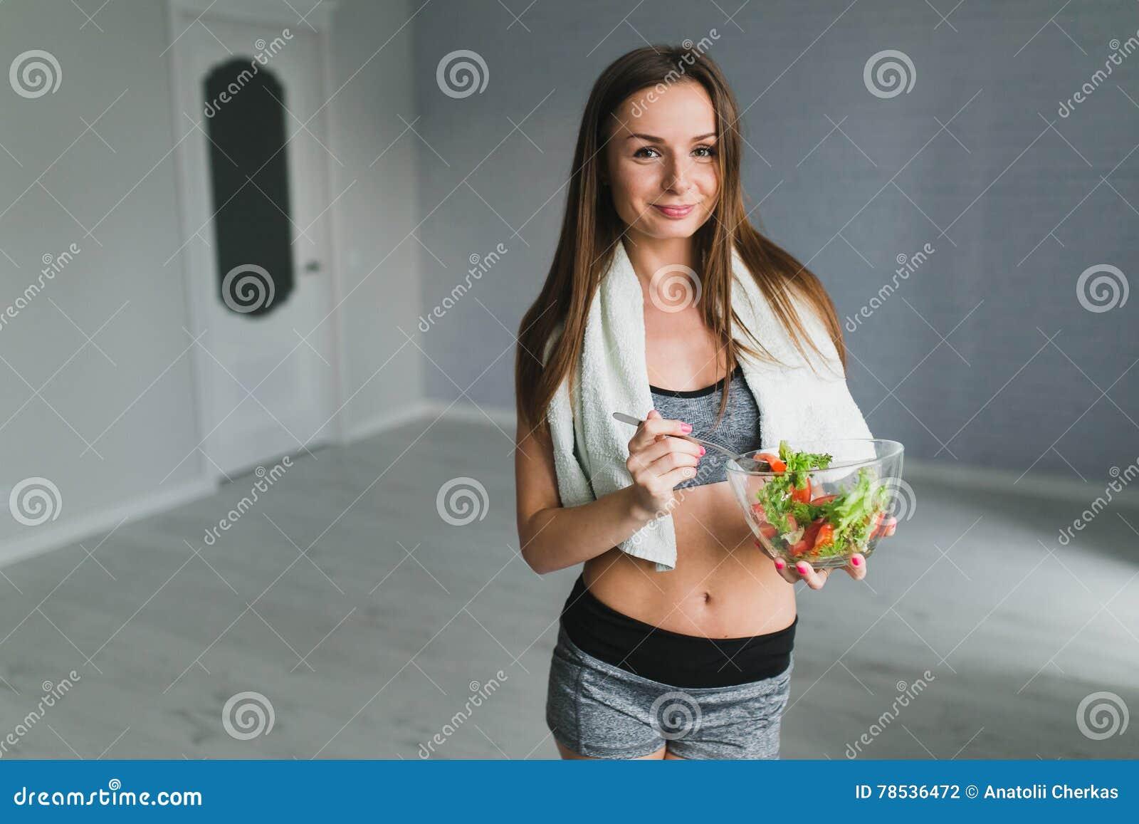 Meisje die en salade na geschiktheid opleiding voorbereiden eten
