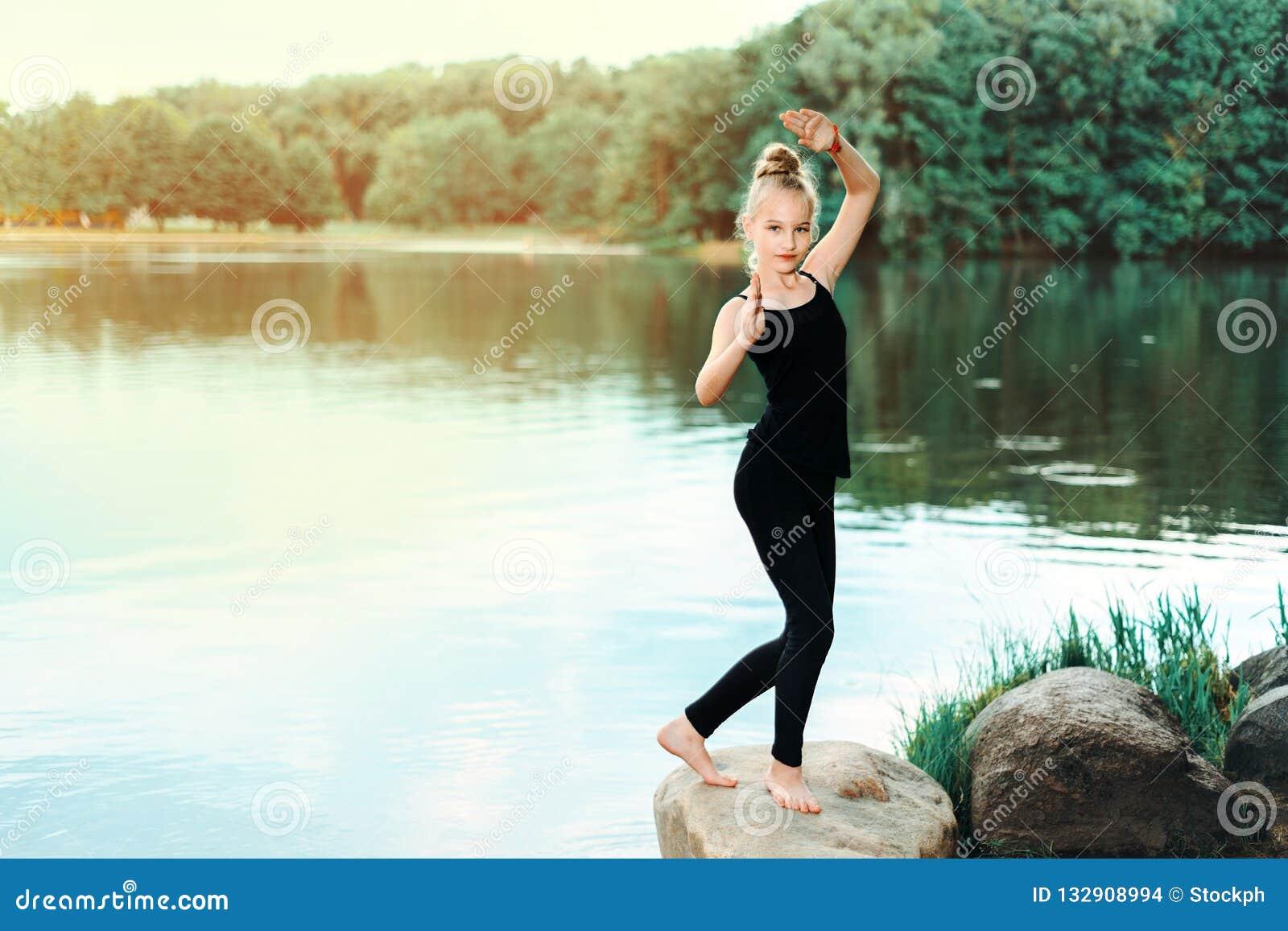 Meisje die geschiktheid, pilates op de rivierbank doen