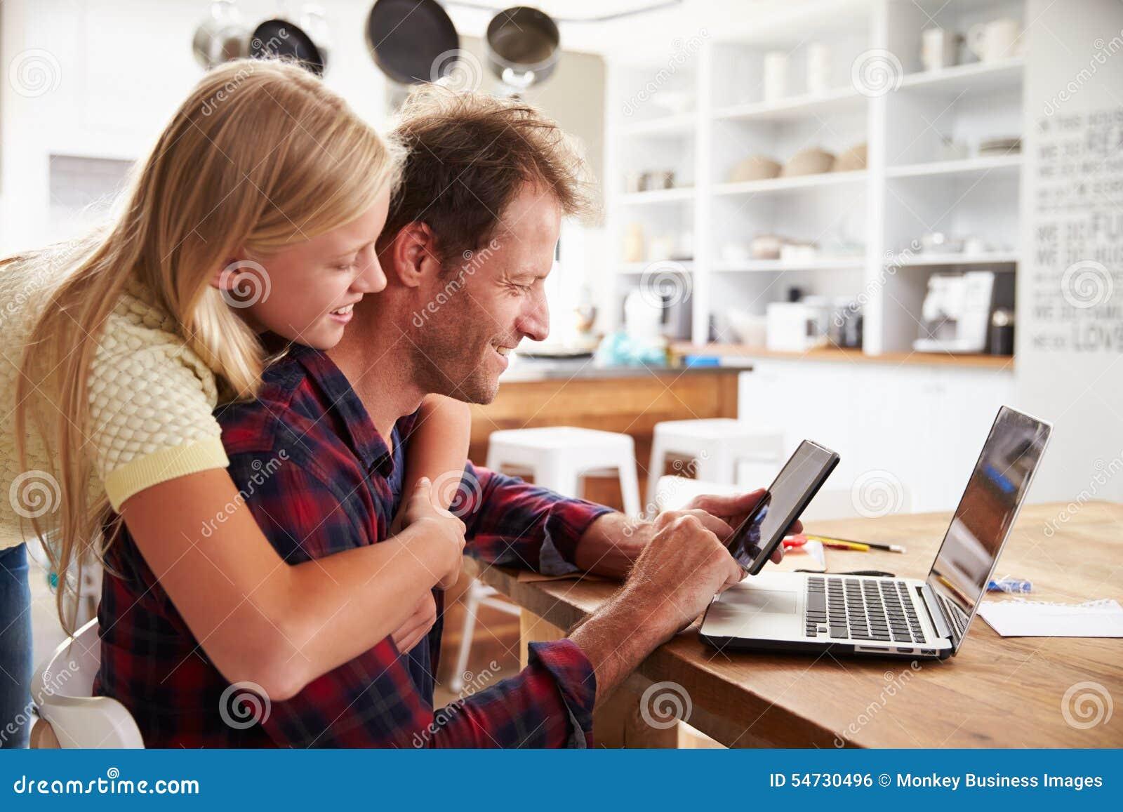 Meisje die haar vader koesteren, die aan laptop thuis werken