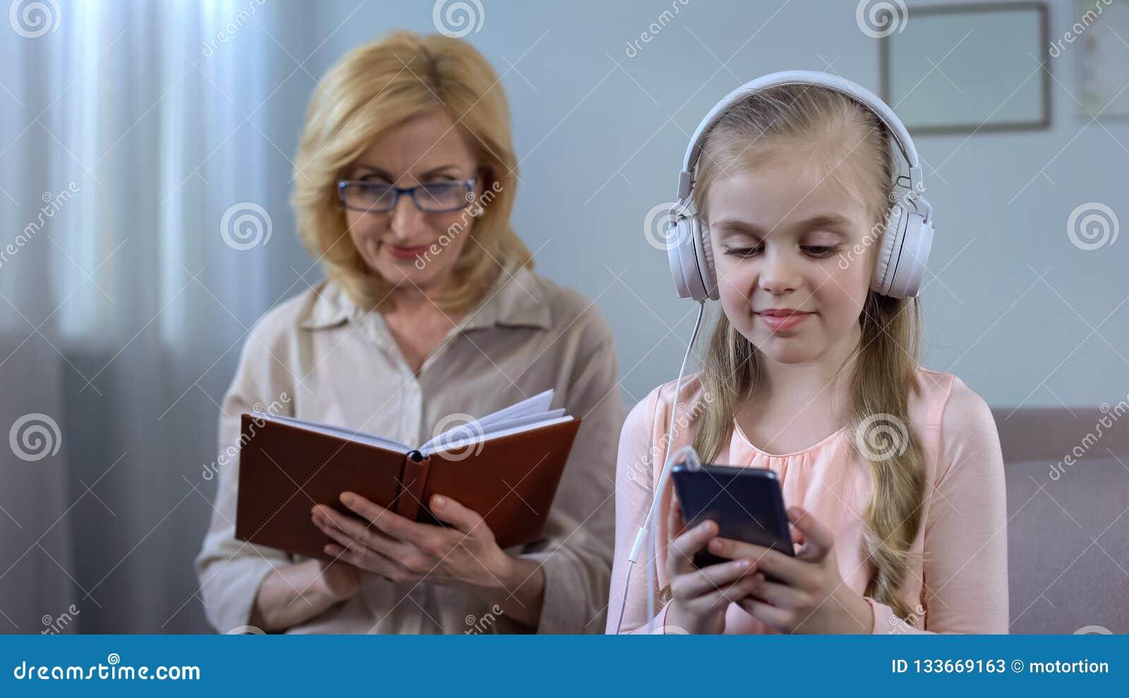 Meisje die in hoofdtelefoons aan de lezing van de het bejaardeoma van het boekverslag luisteren