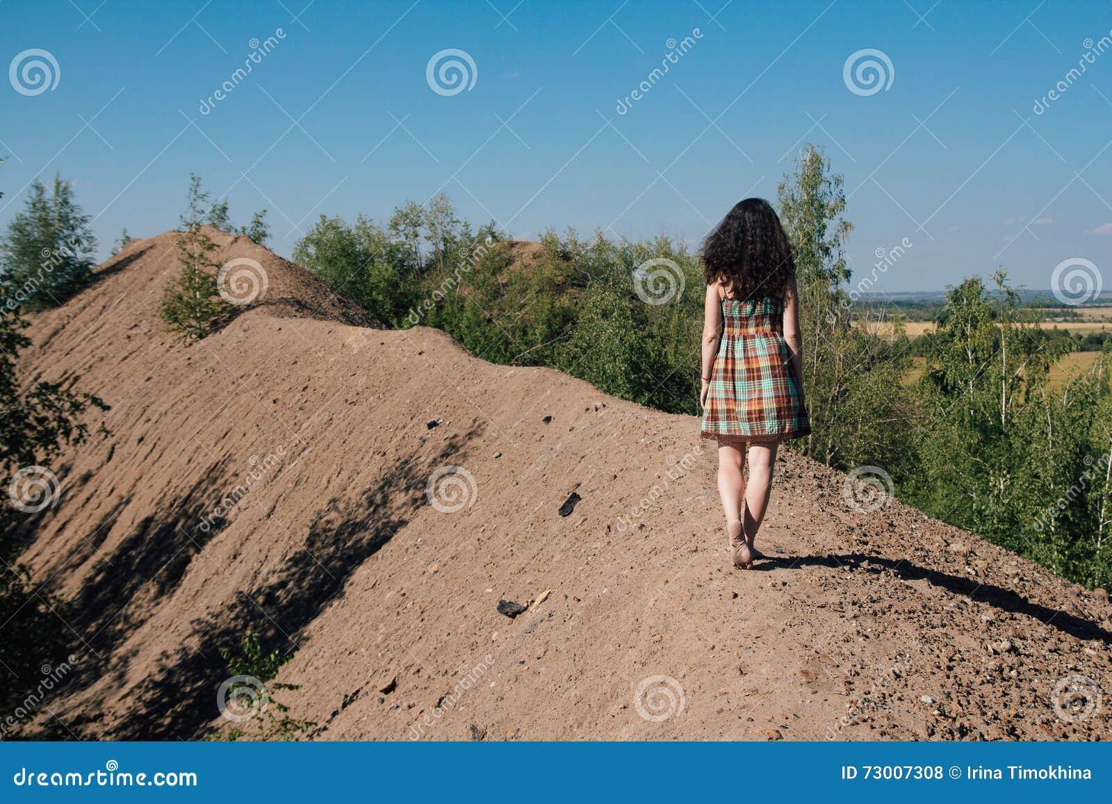 Meisje die in kleding langs de bovenkant van de berg lopen