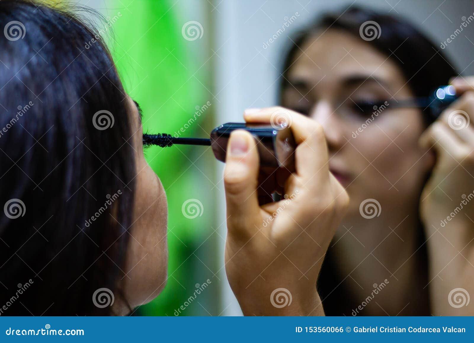 Meisje die mascara in de spiegel toepassen