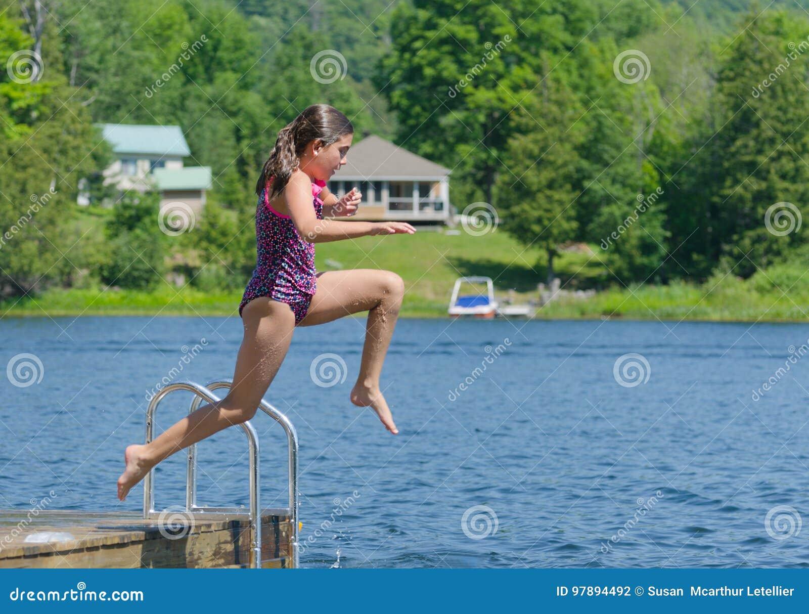 Meisje die in meer van dok bij plattelandshuisje springen