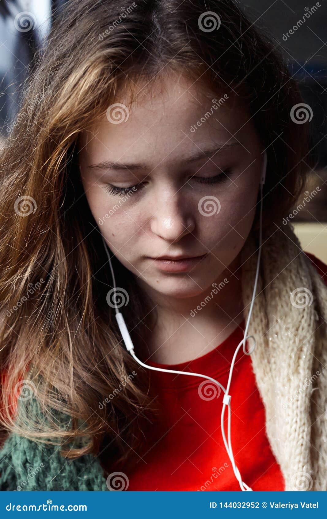 Meisje die met roodbruin haar aan muziek met zijn gesloten ogen luisteren