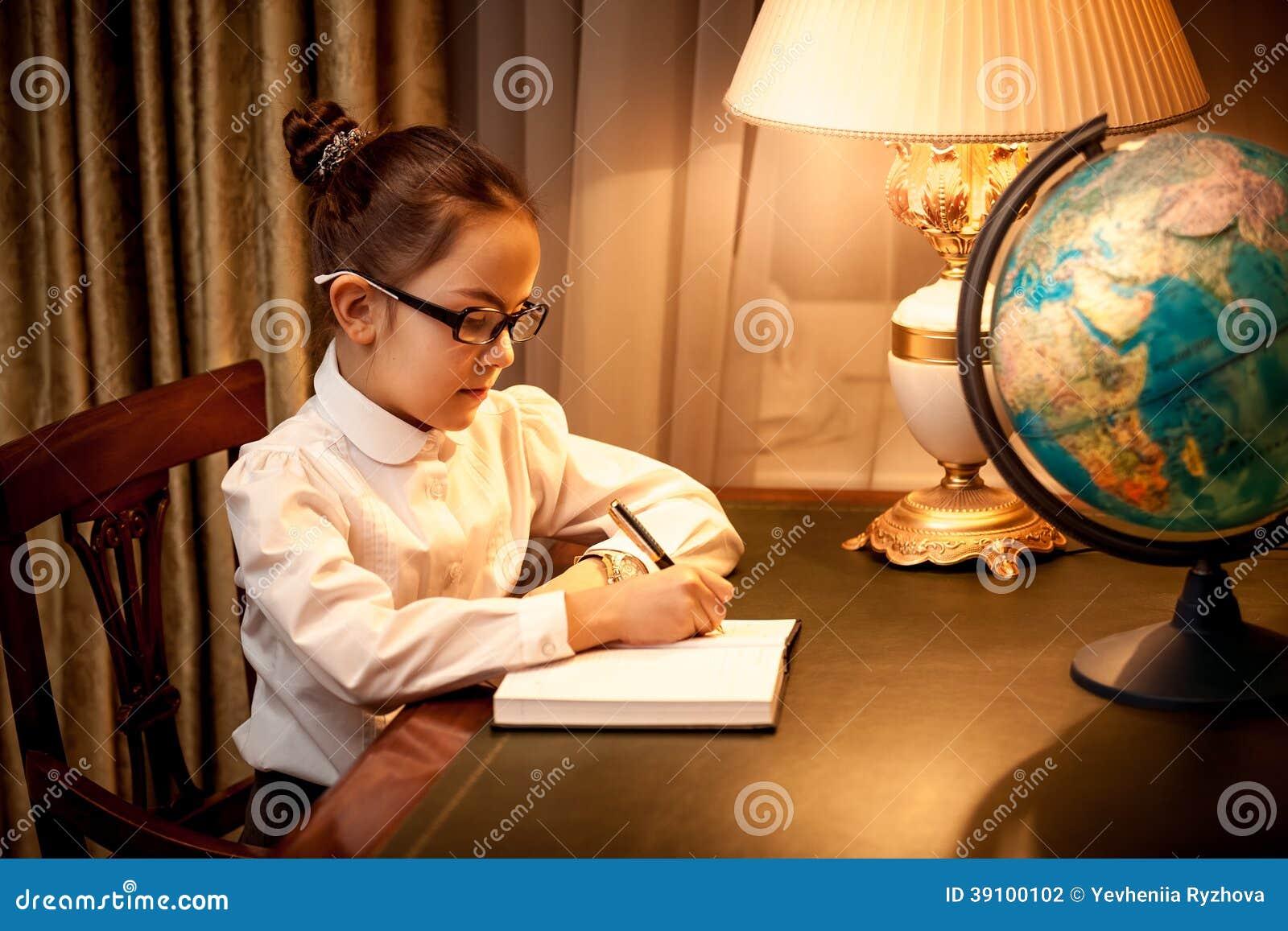 Meisje die in notitieboekje bij bureau met bol schrijven