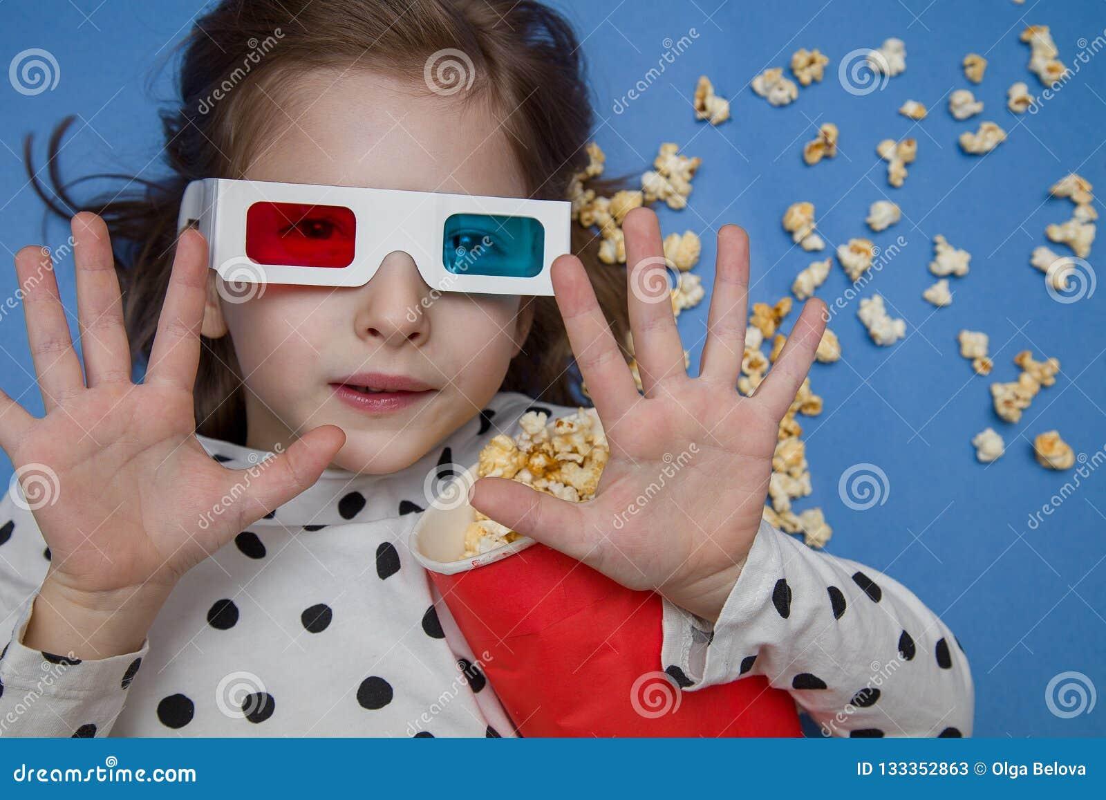 Meisje die op een film in 3D glazen met popcorn letten