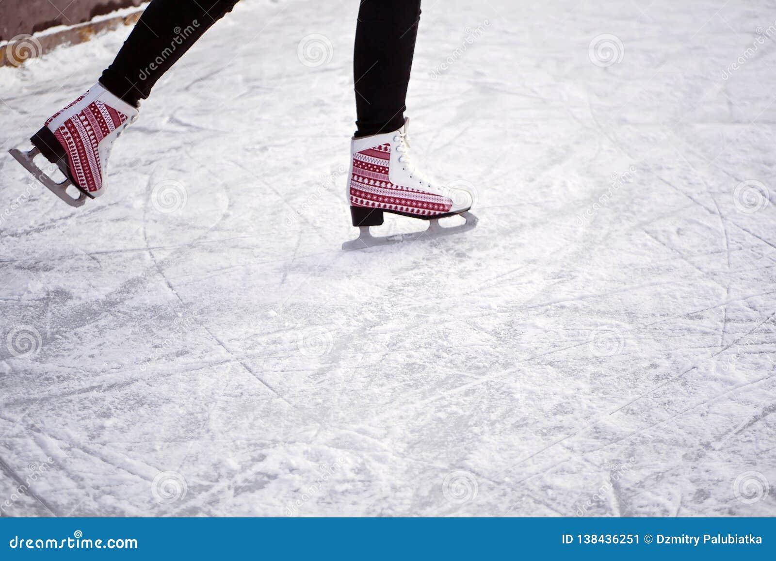 Meisje die op een ijsbaan berijden Ijs en vleten Man voeten in vleten