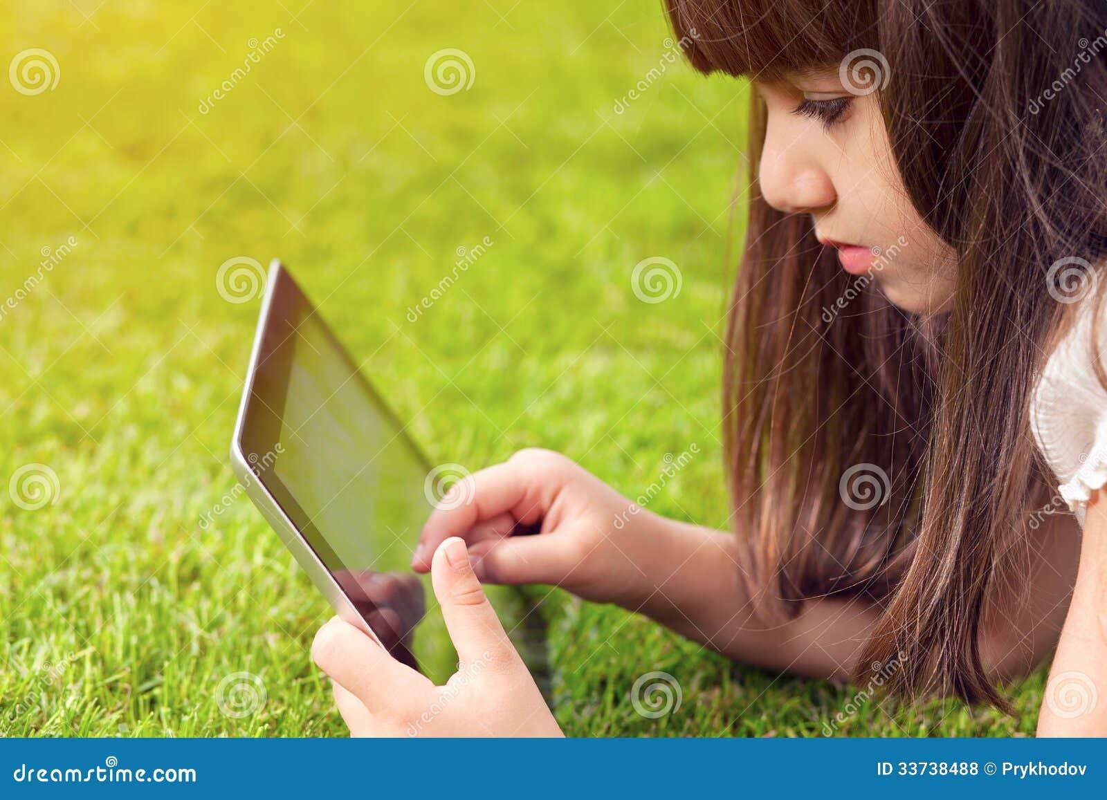 Meisje die op gras en aanrakingen liggen het scherm een tablet