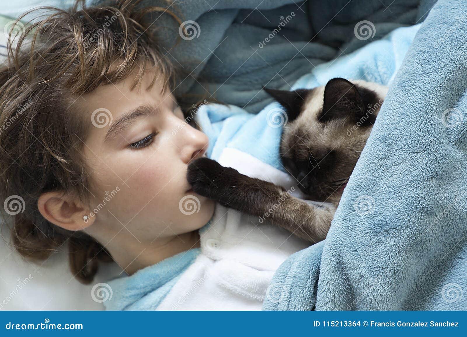 Meisje die op het bed met haar kat liggen