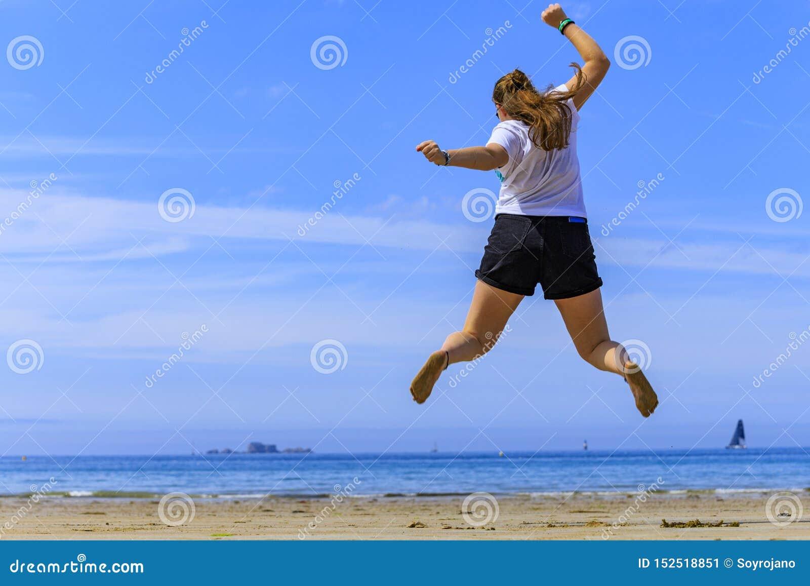 Meisje die op het strand springen