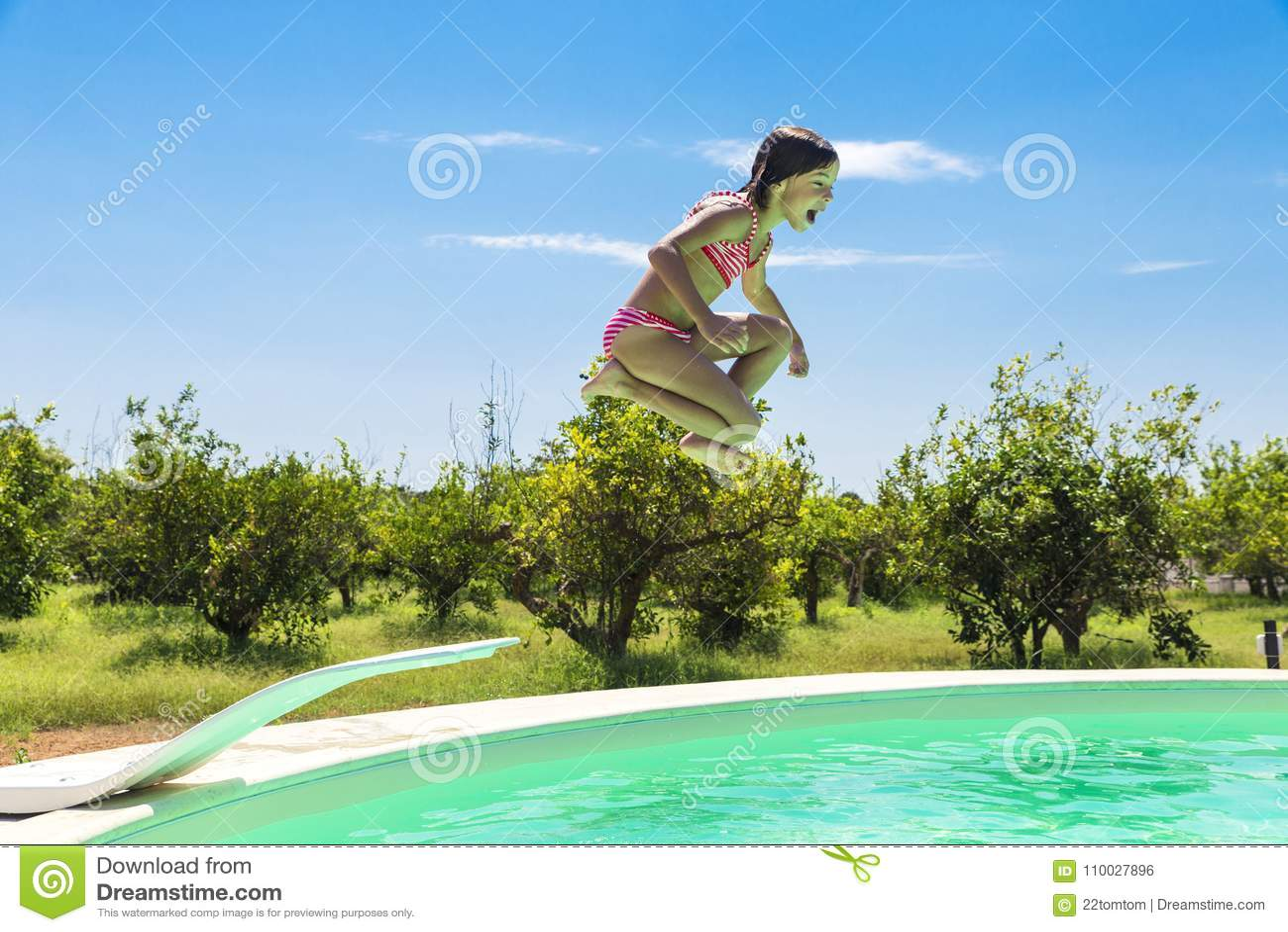 Meisje die in pomp in een openluchtpool springen