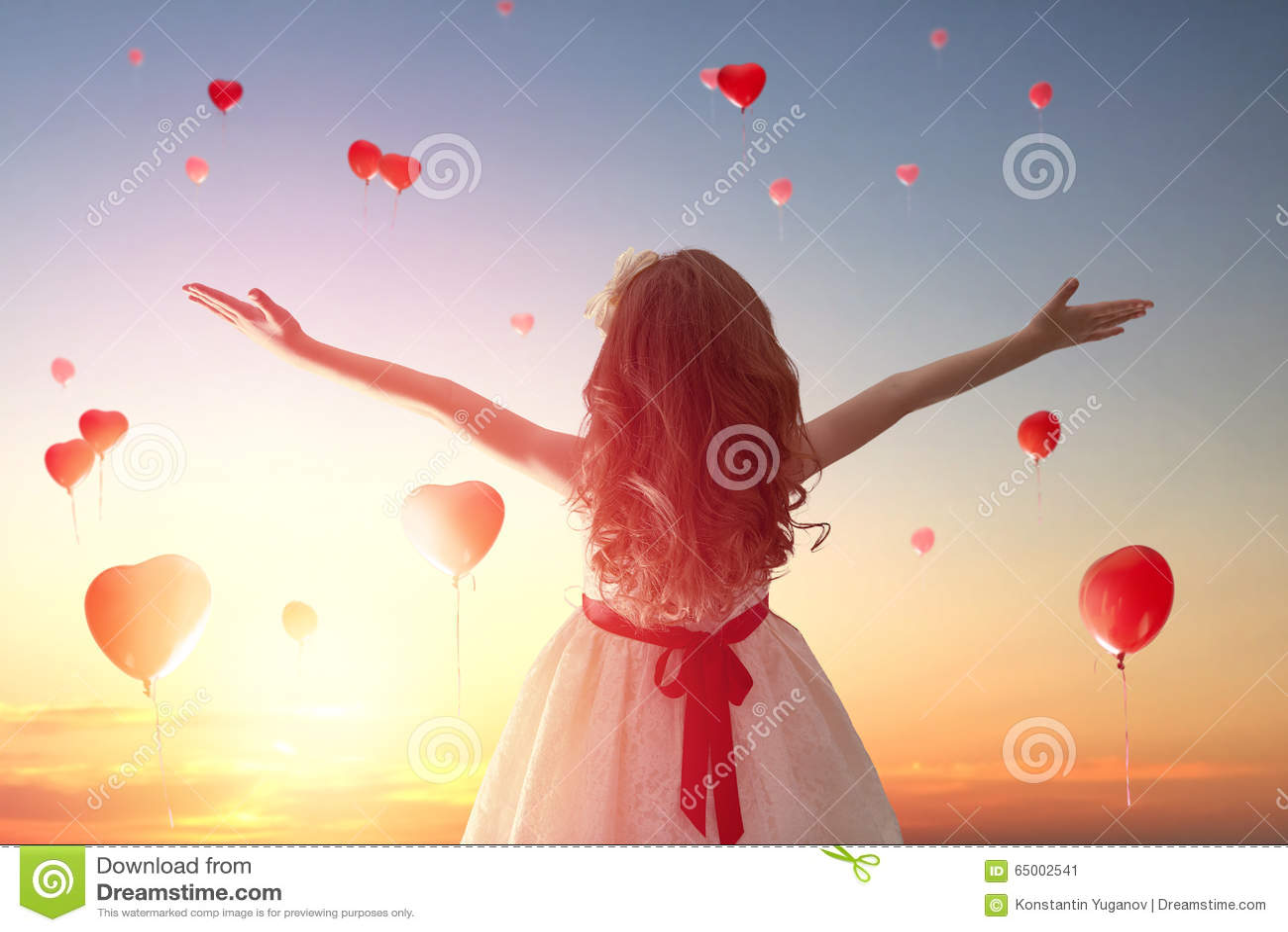 Meisje die rode ballons bekijken