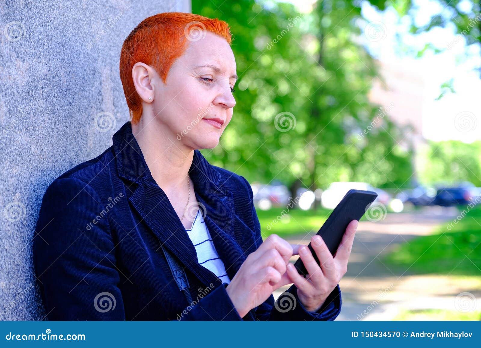 Meisje die SMS in smartphone lezen De emotie van blije verrassing Het korte kapsel van vrouwen Modieus modieus profiel met