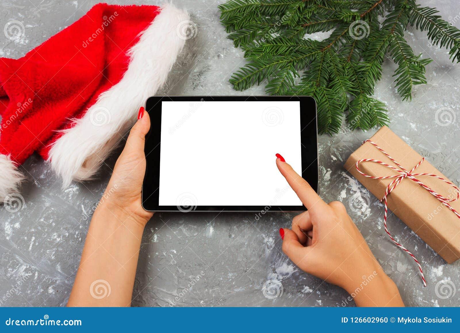 Meisje die tablettechnologie in huis, de computer van de persoonsholding op achtergrondkerstmisdecoratie gebruiken, vrouwelijke h