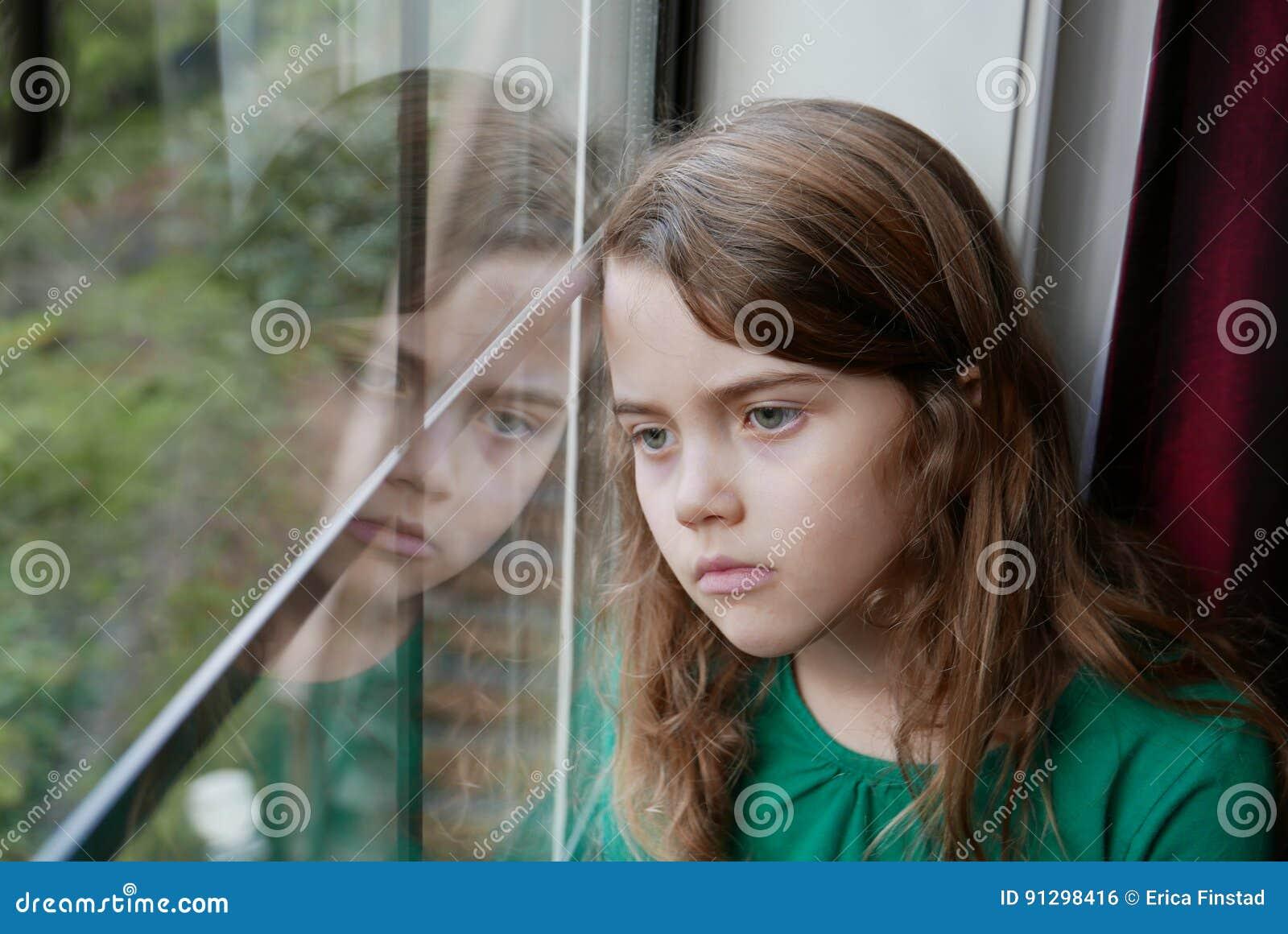Meisje die uit een venster met een droevige uitdrukking kijken