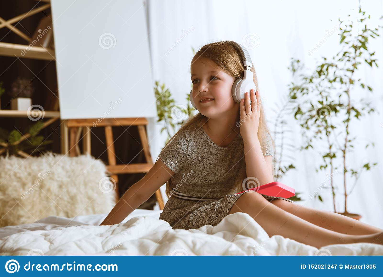Meisje die verschillende gadgets thuis gebruiken