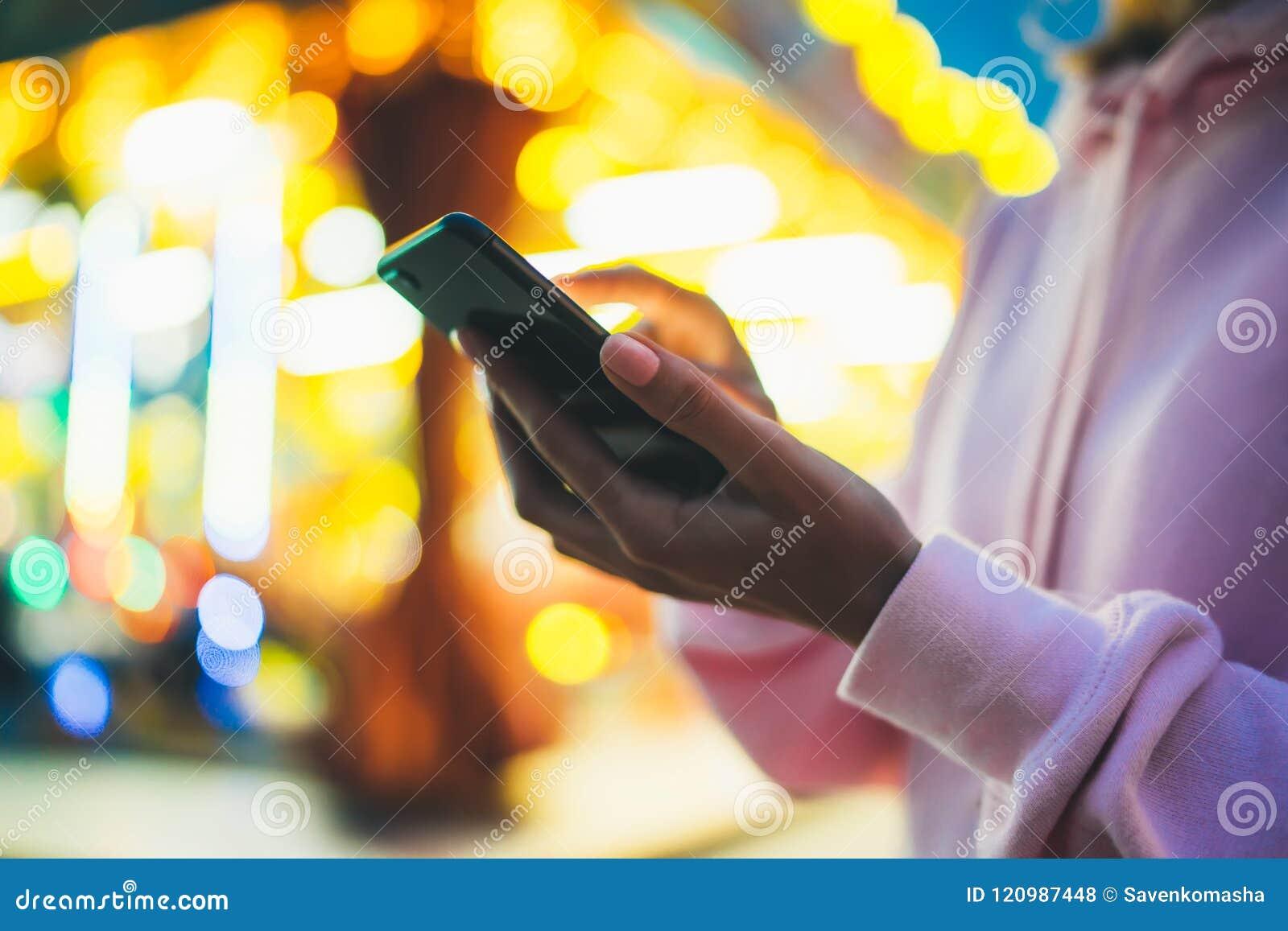 Meisje die vinger op het schermsmartphone richten op achtergrond bokeh licht in verlichting van de nacht de atmosferische stad in
