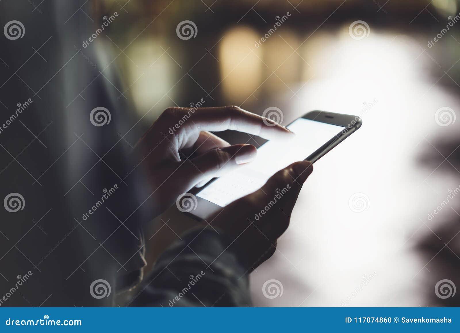 Meisje die vinger op het schermsmartphone richten op het licht van de achtergrondverlichtingsgloed bokeh in stad van nacht de atm
