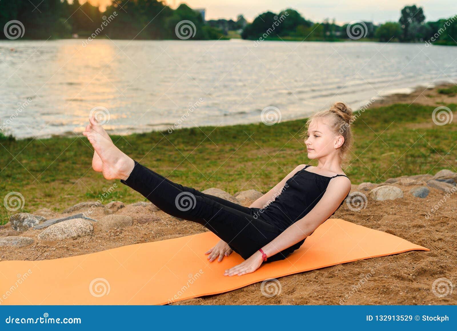 Meisje die yoga doen bij zonsondergang door rive