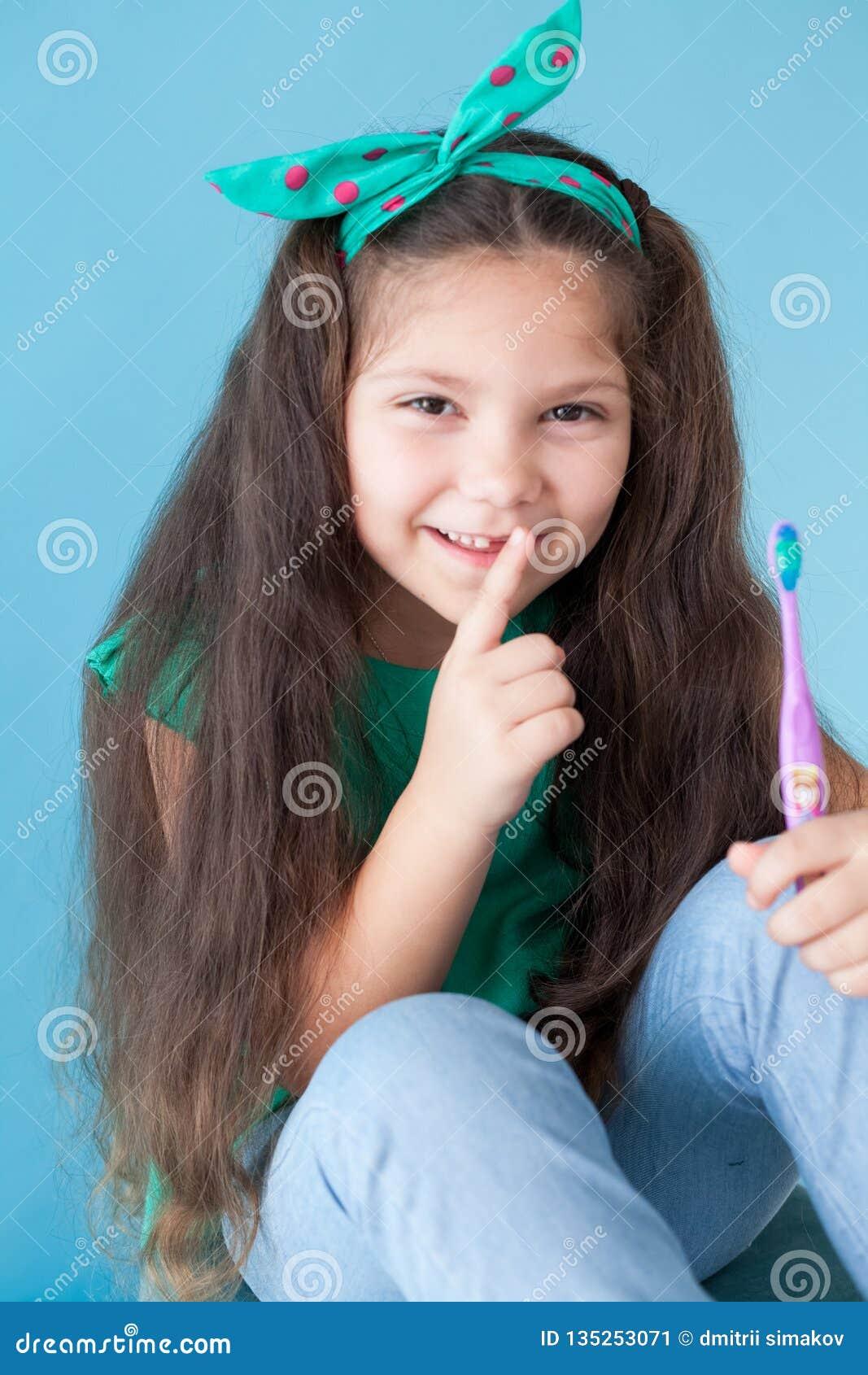 Meisje die zijn tanden met een tand van de tandenborsteltandheelkunde borstelen