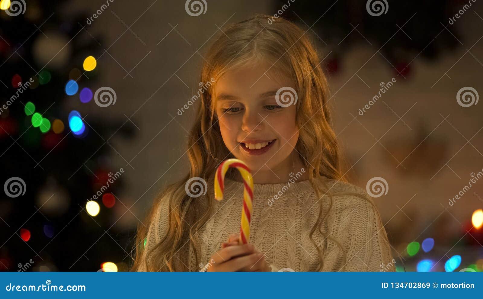 Meisje die zoet smakelijk suikergoedriet houden, die Kerstmis van snoepjes, kinderjaren genieten