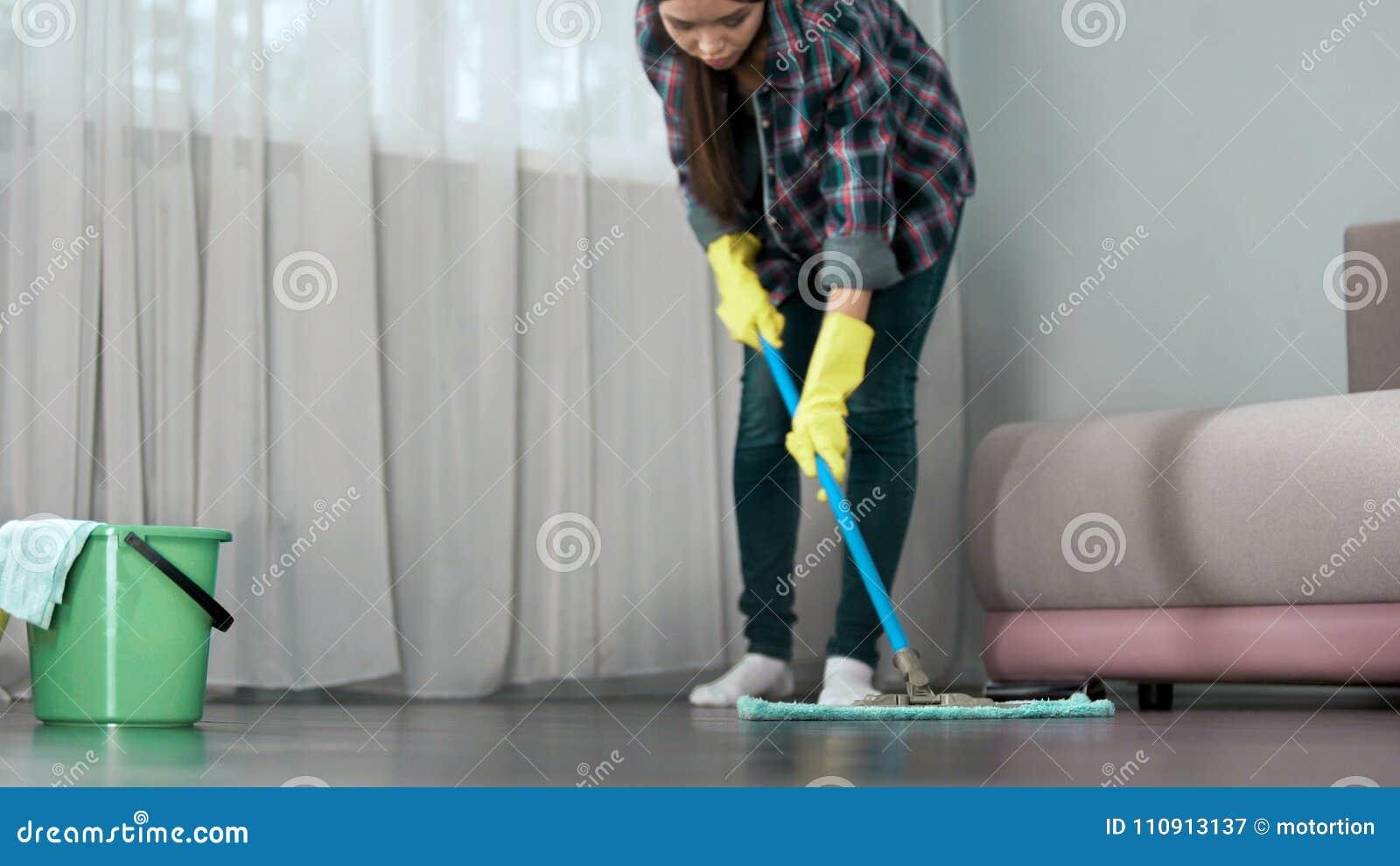 Meisje die zorgvuldig vloer van hotelruimte wassen vóór aankomst van gasten, het schoonmaken