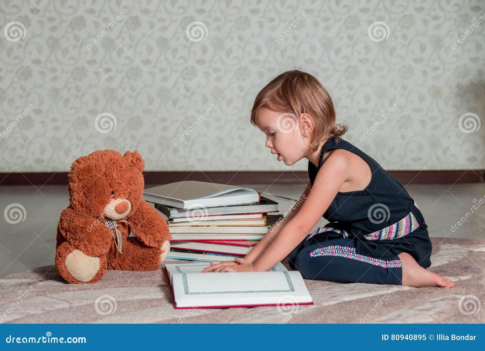 Meisje in donkerblauwe het boekzitting van de kledingslezing op de vloer dichtbij teddybeer Het kind leest verhaal voor stuk spee