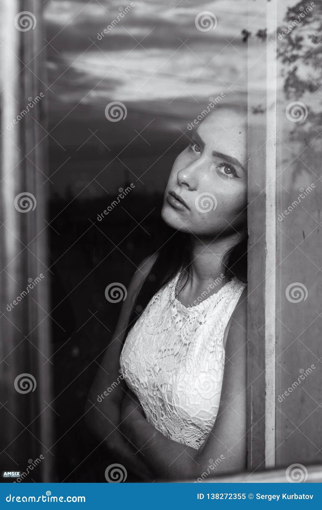 Meisje door het venster in een blokhuis met schemerige lichte zwart-witte kleuren