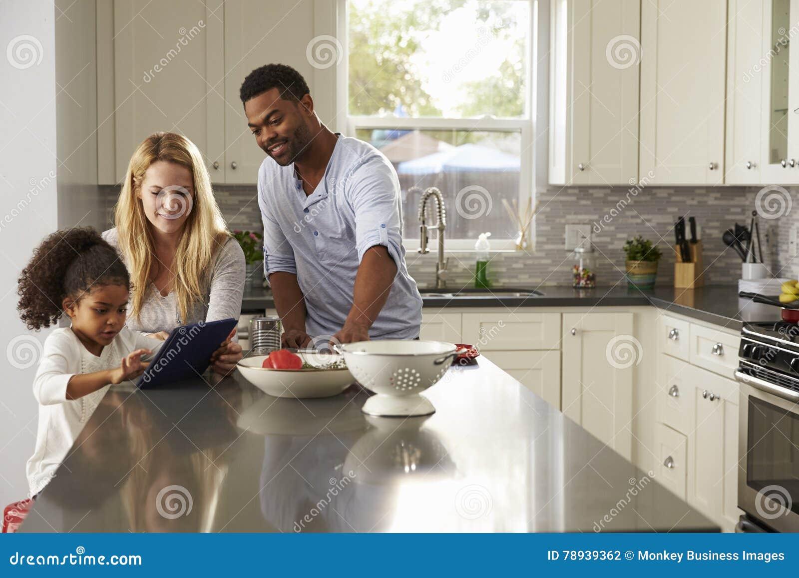 Meisje en de gemengde computer van de het gebruikstablet van rasouders in keuken