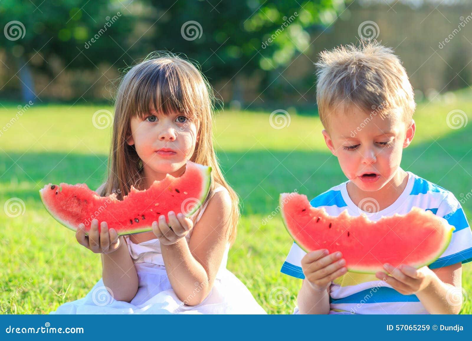 Meisje en een jongen die watermeloen eten