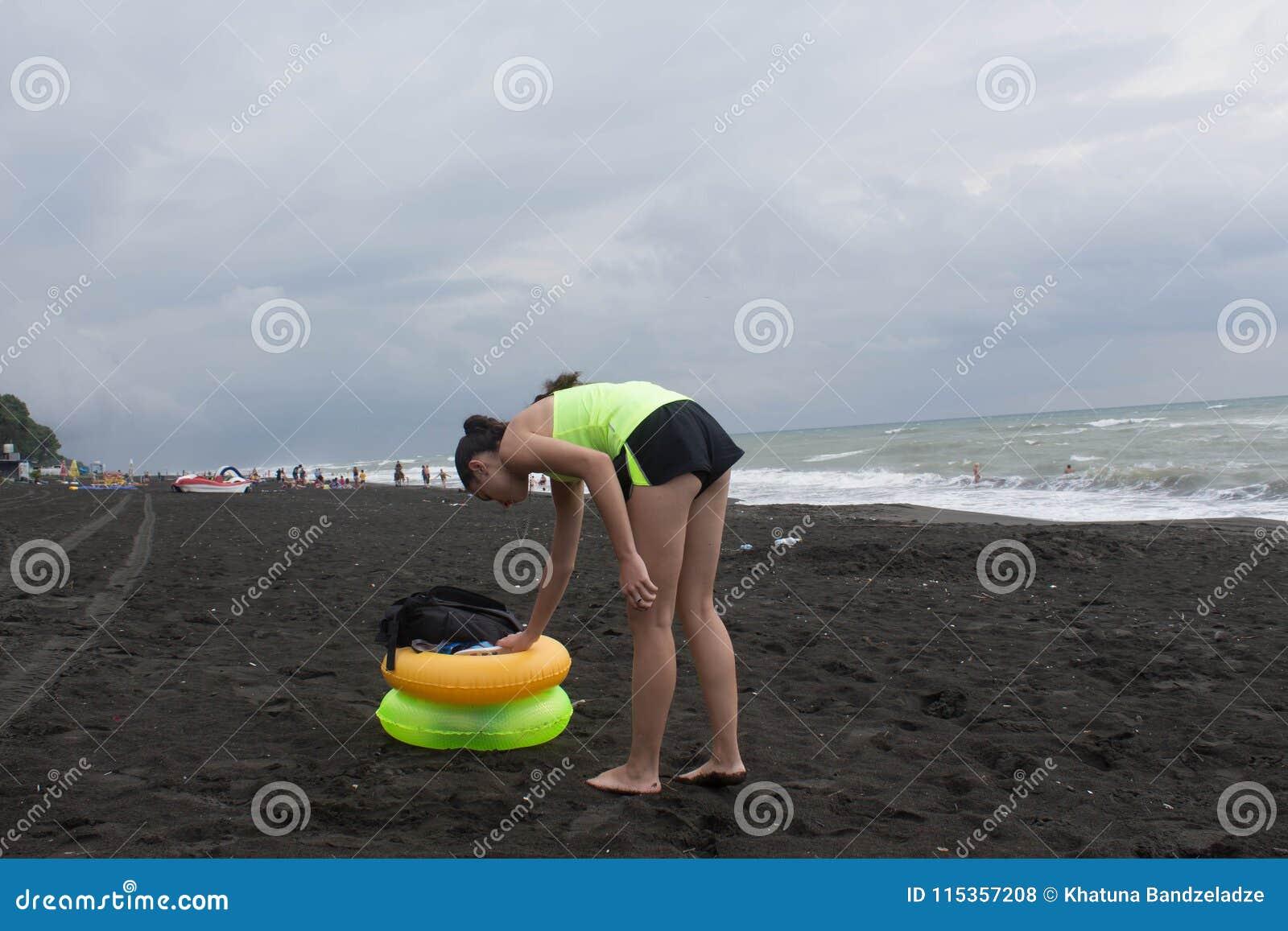 Meisje en gele, groene Drijvende Ring op strand, bewolking, wolken, golven
