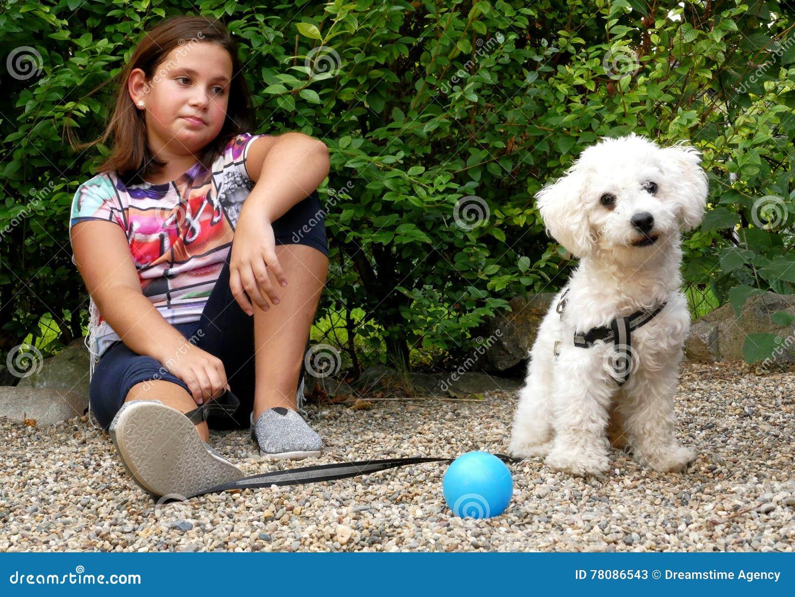 Meisje en haar hond in de tuin