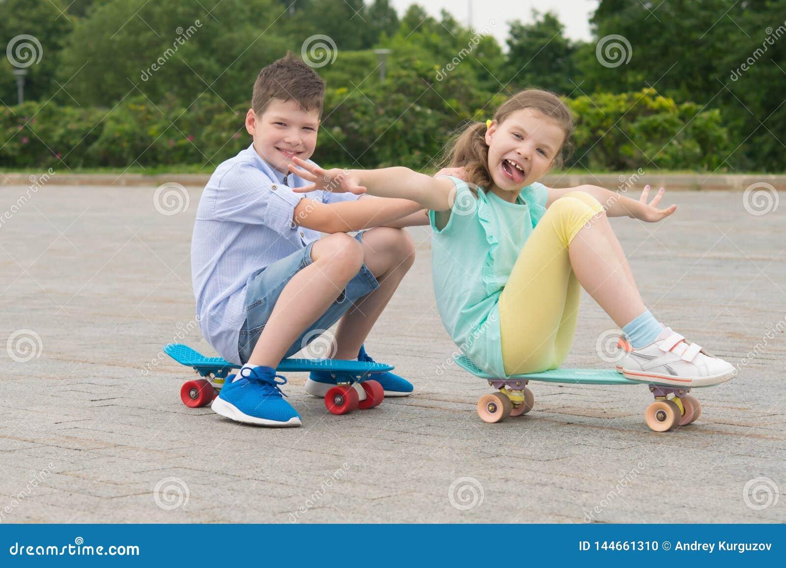 Meisje en jongen in het Park die in openlucht, zitting op sportenraad, de bouw grappige grimassen berijden
