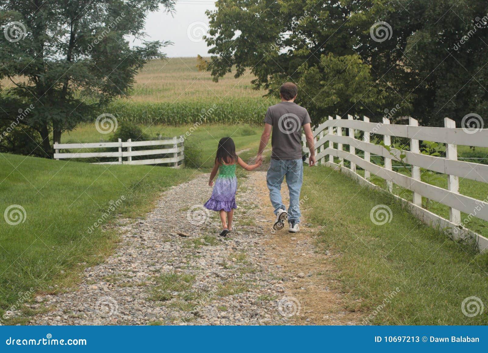 Meisje en papa die op weg lopen