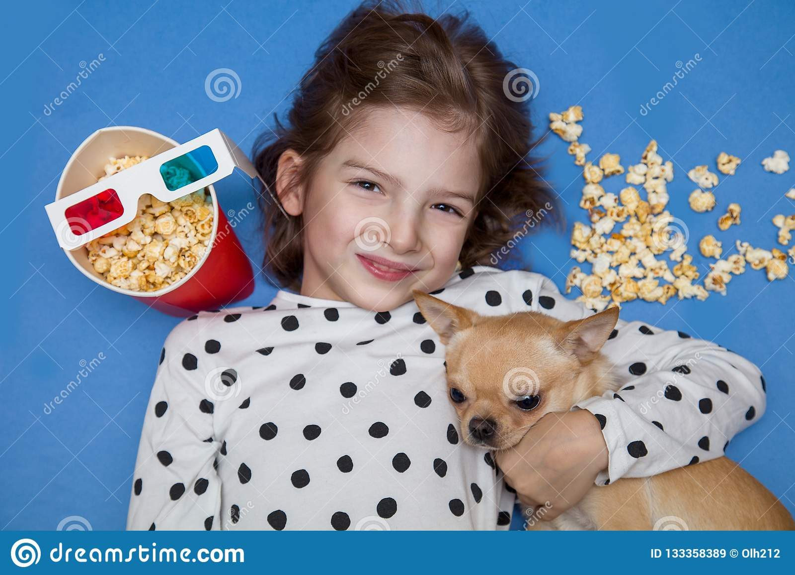 Meisje en weinig hond het letten op film in 3D glazen met popcorn