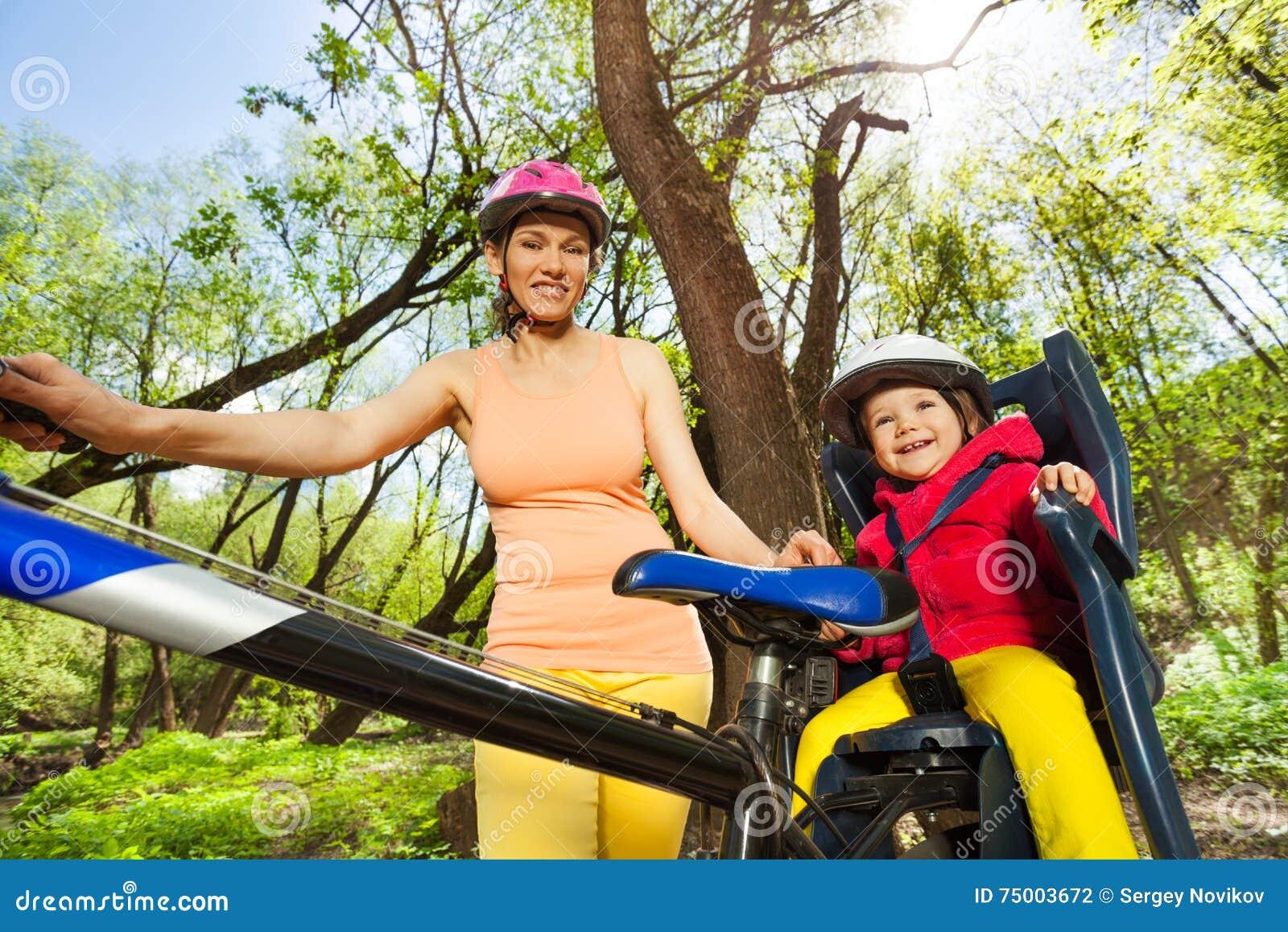 Meisje in fietszetel in openlucht met haar moeder