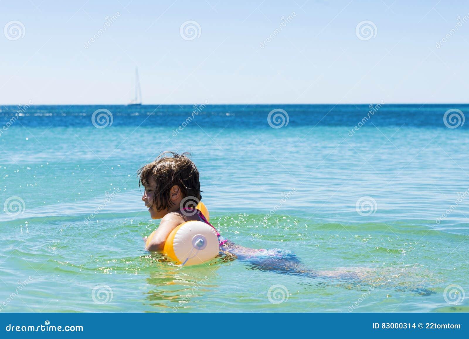 Meisje het baden met een vlotter op het strand