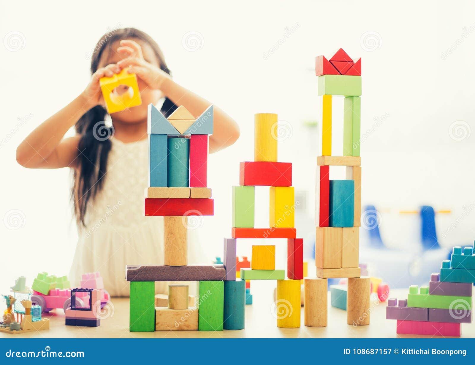 Meisje in het kleurrijke overhemd spelen met bouwstuk speelgoed blokken die een toren bouwen Jonge geitjes met raad Kinderen bij