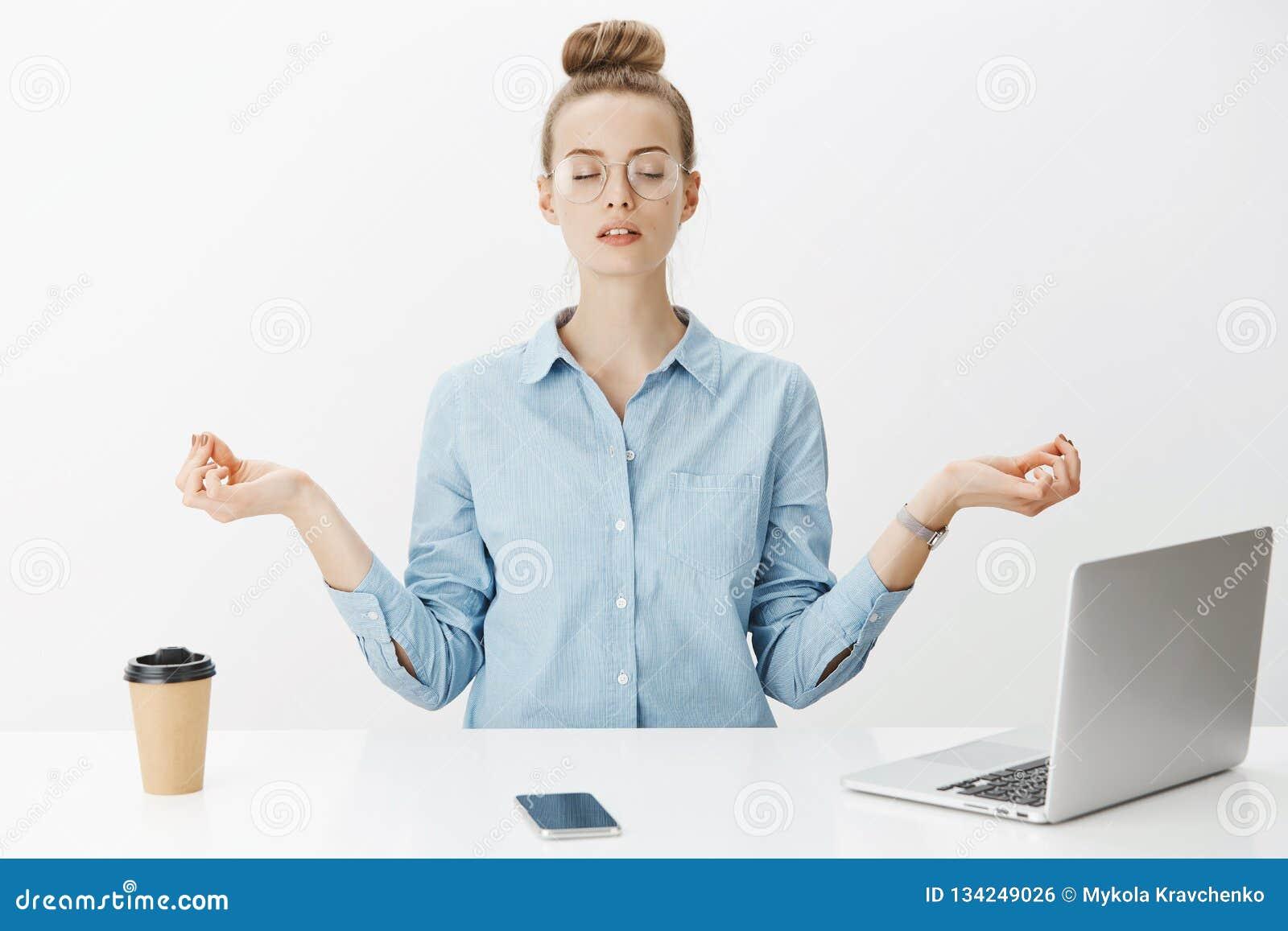 Meisje het mediteren bij het werkzitting in lotusbloem stelt met nirvanaorbs dichtbij laptop en smartphone het proberen ontspant