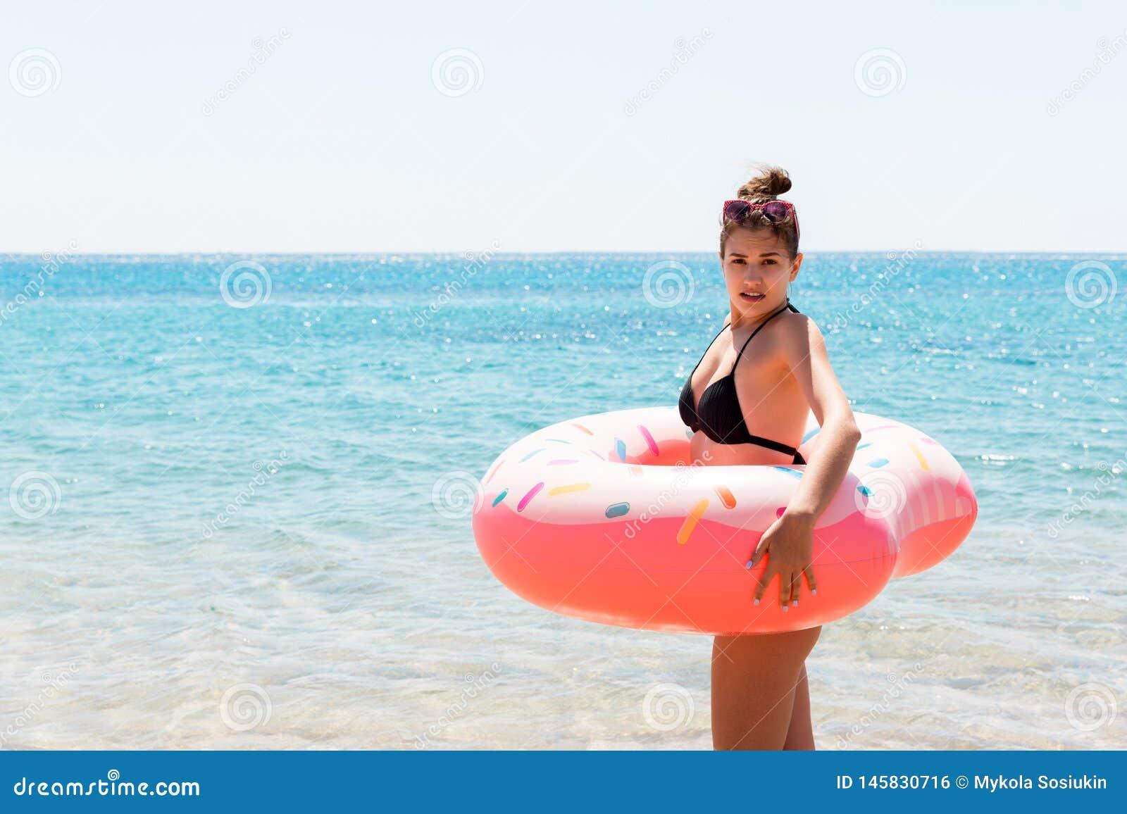 Meisje het ontspannen met opblaasbare ring op het strand geschokt of verrast meisje in het koude overzees De zomervakantie en vak
