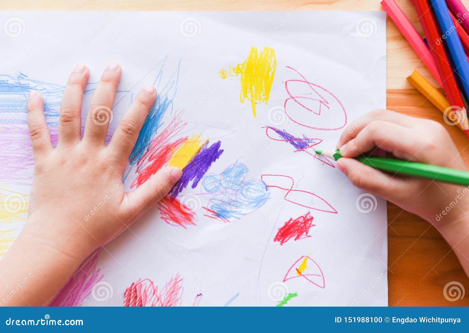 Meisje het schilderen op document blad met kleurenpotloden op de houten lijst thuis - kindjong geitje die tekeningsbeeld en kleur